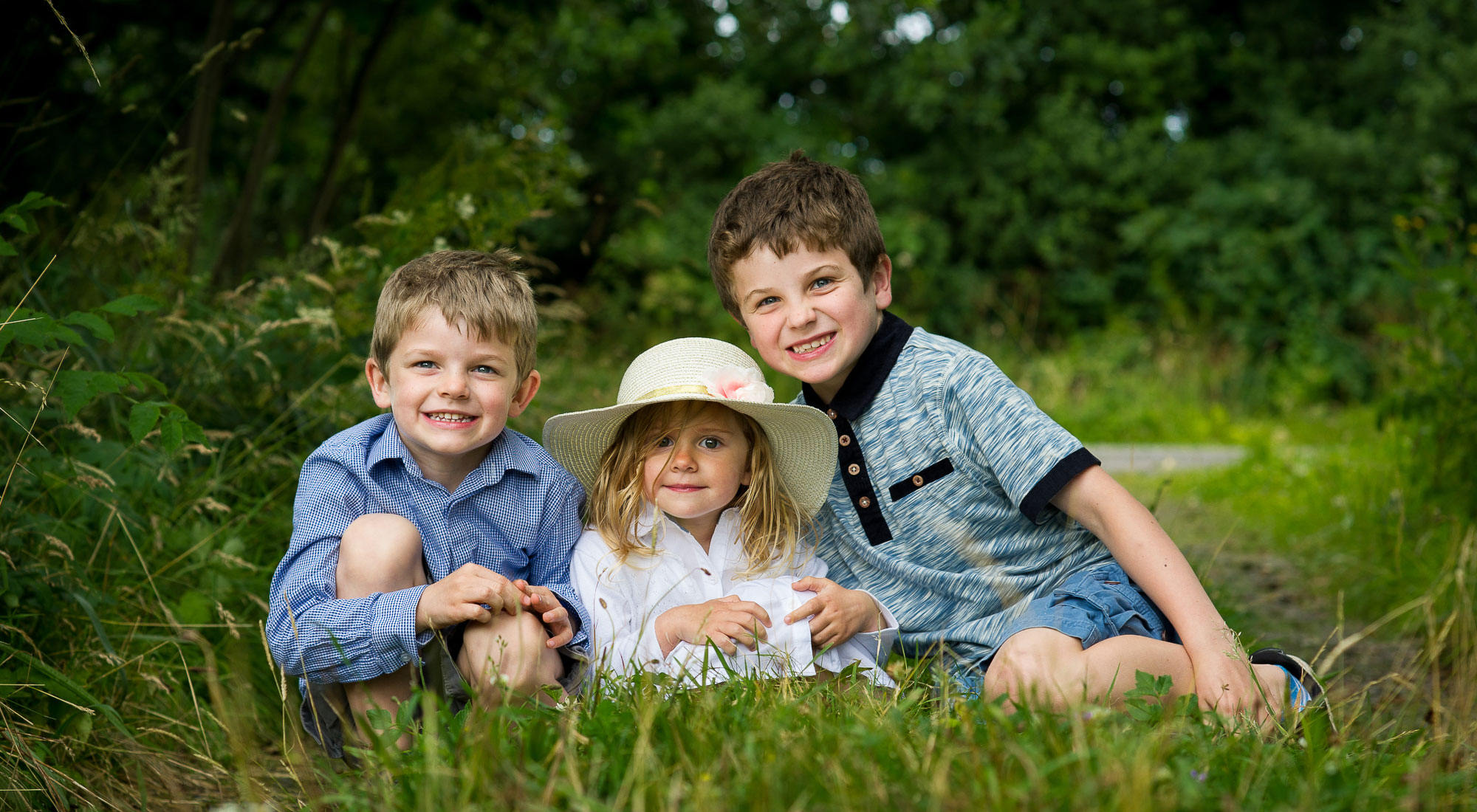 Family siblings sitting in the grass