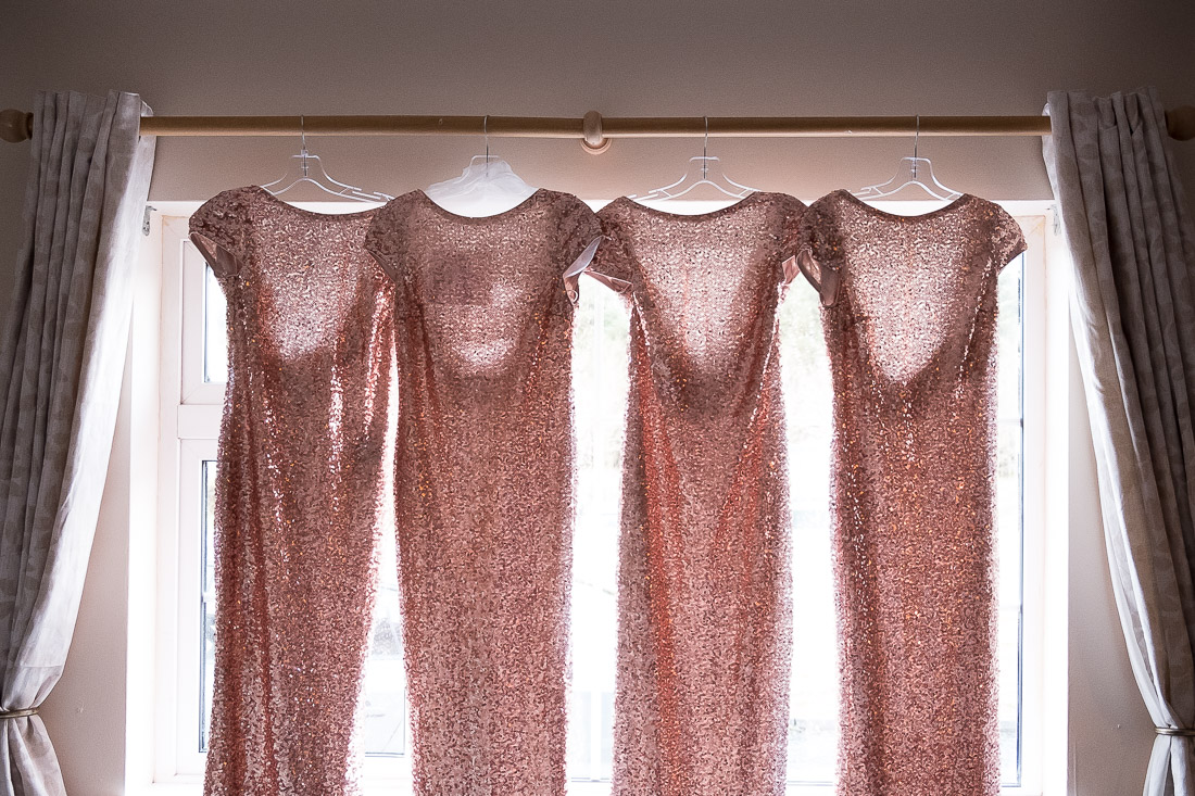 Bridesmaid's dresses hanging by window