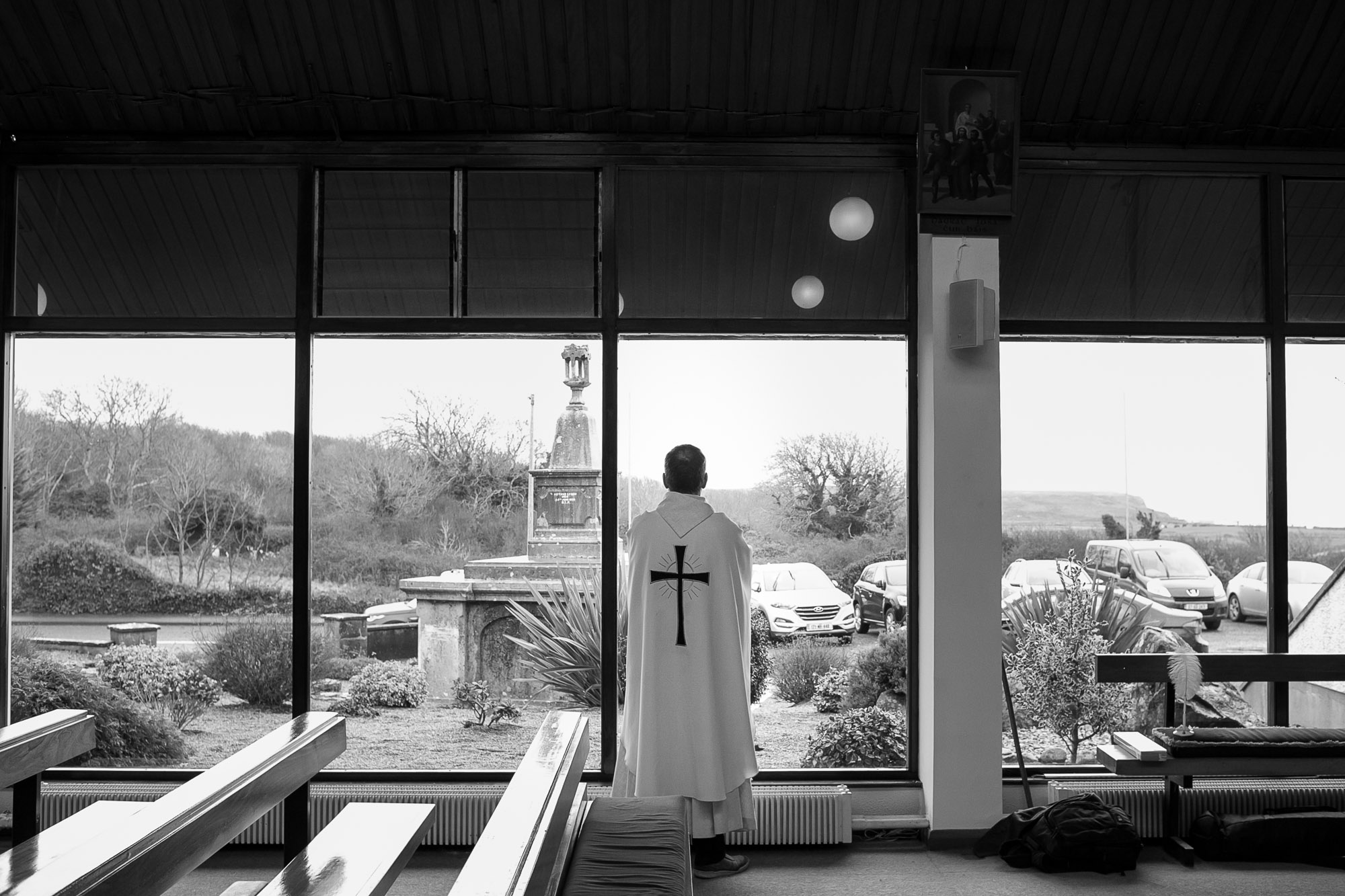Priest looking out window